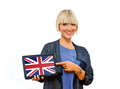 Attractive blond woman holding tablet with united kingdom flag on screen Royalty Free Stock Photography