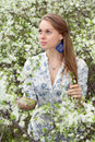 Attractive blond woman in white blouse posing in the garden Royalty Free Stock Photo