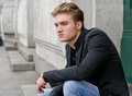 Attractive blond young man in jeans and jacket sitting outdoors looking off camera Stock Photo
