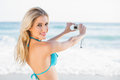 Attractive blonde in bikini taking a self picture looking at cam on beautiful sunny beach camera Royalty Free Stock Photos