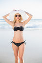 Attractive blonde in bikini wearing straw hat and sunglasses on a beautiful sunny beach Stock Images