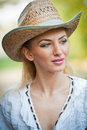 Attractive blonde girl with straw hat and white blouse beautiful young woman kaftan against a brick wall Royalty Free Stock Photography