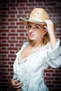 Attractive blonde girl with straw hat and white blouse beautiful young woman kaftan against a brick wall Royalty Free Stock Images