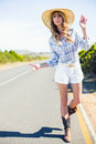 Attractive blonde hitchhiking at the roadside in summertime Royalty Free Stock Photos