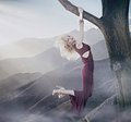 Attractive blonde lady hanging on a tree Royalty Free Stock Image