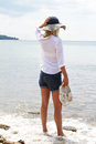 Attractive Blonde Woman wearing white shirt and straw standing and enjoying view on the beach near sea Royalty Free Stock Photo