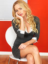 Attractive bored business woman sitting in a chair fed up her twenties with long blonde hair wearing short mini dress showing Royalty Free Stock Images