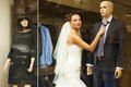 The attractive bride in showcase is touching tie on mannequin Stock Photo