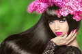 Attractive Brunette Girl with Flowers Long Hair. Healthy Black H Royalty Free Stock Photo