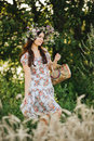 Attractive brunette girl with long hair wearing dress in floral print with wrath of wildflowers on head posing outdoor. Woman walk Royalty Free Stock Photo