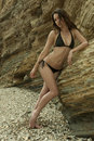 Attractive brunette girl posing sexy in brazilian bikini in front of rocks at palos verdes secret cove beach ca Stock Image