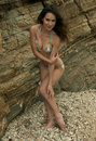 Attractive brunette girl posing sexy in brazilian bikini in front of rocks at palos verdes secret cove beach ca Royalty Free Stock Images