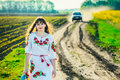 Attractive brunette in Ukrainian national costume on a dirt road on the background of a car