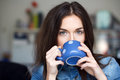 Attractive brunette woman holding blue dotted mug coffee Royalty Free Stock Photography