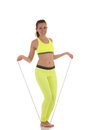 Attractive brunette woman in sports neon yellow bra and leggings doing exercises using a long skipping-rope. Royalty Free Stock Photo