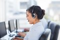 Attractive brunette working in a call centre with her headset Stock Photos