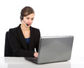 Attractive business woman with headset working on a laptop Royalty Free Stock Photo