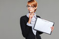 Attractive business woman holding a clipboard and thinking isolated on grey Royalty Free Stock Images