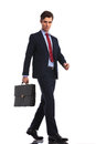 Attractive businessman with suitcase stepping forward Royalty Free Stock Photo