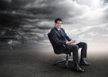 Attractive businessman using his laptop outside during stormy we on a swivel chair weather Stock Image