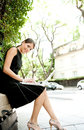 Attractive businesswoman using a laptop computer while sitting in a leafy city street during a sunny day smiling Stock Photography