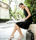Attractive businesswoman using a laptop computer while sitting in a leafy city street during a sunny day smiling Stock Photos