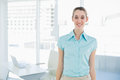 Attractive businesswoman wearing blue blouse posing in her office Royalty Free Stock Photo