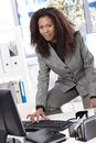 Attractive businesswoman working at desk smiling afro in bright office typing on keyboard Royalty Free Stock Photo