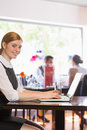 Attractive businesswoman working on laptop smiling at camera in a restaurant Royalty Free Stock Photo