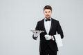 Attractive butler in tuxedo standing and holding silver empty tray Royalty Free Stock Photo