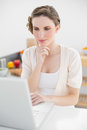 Attractive calm woman sitting thoughtful in front of her laptop kitchen Stock Photos