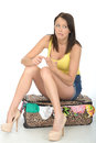 Attractive Confused and Concerned Young Woman Sitting on a Suitcase Royalty Free Stock Photo