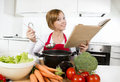 Attractive cook woman preparing vegetable stew soup reading recipe cookbook at domestic kitchen Royalty Free Stock Photo