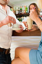Attractive couple in cafe or coffeeshop the background the barista to be seen Stock Image