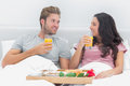 Attractive couple having breakfast in bed with orange juice and cereals Royalty Free Stock Image