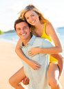 Attractive couple playing on the beach at sunset happy Stock Photography