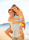 Attractive couple playing on the beach at sunset happy Stock Images