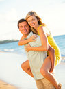 Attractive couple playing on the beach at sunset happy Royalty Free Stock Images