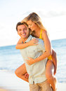 Attractive couple playing on the beach at sunset happy Royalty Free Stock Photos