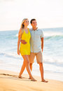 Attractive couple playing on the beach at sunset happy walking romantic vacation Royalty Free Stock Photography