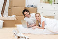 Attractive couple relaxing while moving house lying on a mattress on a bare wooden floor surrounded by packing boxes smiling at Royalty Free Stock Images