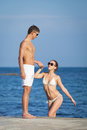 Attractive couple at the sea young men and women on seashore in day time Stock Photography