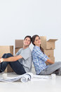 Attractive couple sitting back to back in their new house Stock Photo