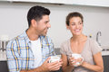 Attractive couple sitting having coffee together at home in kitchen Stock Photo