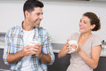 Attractive couple sitting having coffee together and laughing at home in kitchen Royalty Free Stock Photo