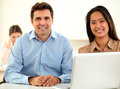 Attractive coworker couple smiling at you portrait of while sitting on office desk Stock Photography