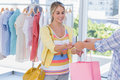 Attractive customer receiving her credit card and shopping bags Stock Images