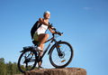 Attractive cyclist on bike young beautiful girl a mountain and the blue sky in the park Royalty Free Stock Photography