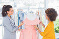 Attractive fashion designers adjusting a dress on mannequin Stock Photo