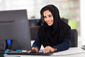 Attractive female arabic corporate worker working computer Royalty Free Stock Photography
